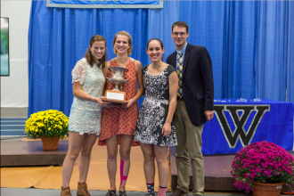 Seniors Sara Vannah, Sonja Cwik and Edie Sharon celebrate their Seven Sisters Championship with Coach Phil Jennings at the luncheon following the race. Photo courtesy of Wellesley Blue