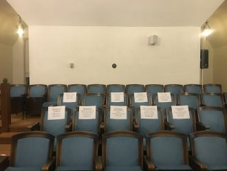 Image of empty seats at town hall, reserved for senior administration.