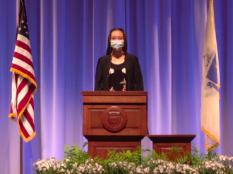 College Government President Tatiana Ivy Moise '21 speaks at commencement. She wears a mask and a graduation robe, and stands at a podium.