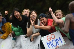 People with signs cheering on runners