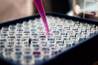 a pipette filled with pink liquid being emptied in vials